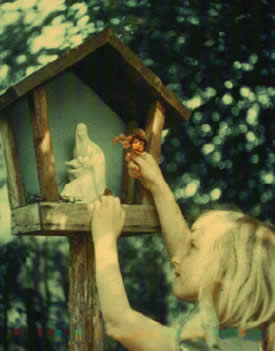 A child makes an offering to Our Lady at a wayside shrine